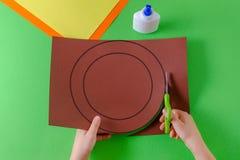 De handen van het kind snijden cirkel op pakpapier met schaar, hoogste mening, op groen royalty-vrije stock afbeeldingen