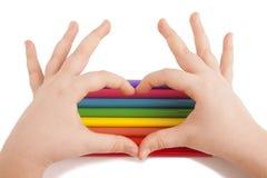 De handen van het kind vormen een hartvorm boven kleurenpotloden Stock Foto's