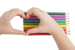 De handen van het kind vormen een hartvorm boven kleurenpotloden Stock Afbeeldingen