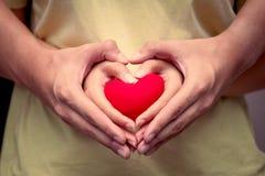 De handen van het liefdepaar met rood hart royalty-vrije stock afbeeldingen