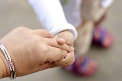 De handen van het mamma en van het jonge geitje Stock Fotografie