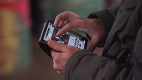 De handen van het mannetje houden minitablet met geval en kranen op zijn aanrakingsvertoning stock video