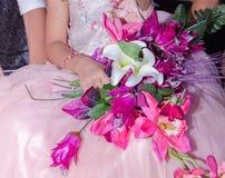 De handen van het meisje in een roze kleden zich met een boeket van kunstbloemen bij een huwelijk Royalty-vrije Stock Fotografie