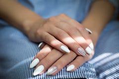 De handen van het meisje met huwelijksmanicure op de blauwe achtergrond Close-upvrouw die haar handen met mooie manicure tonen stock afbeelding