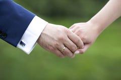 De handen van de het paarholding van het huwelijk Stock Afbeeldingen