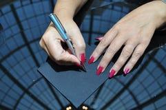 De handen van het wijfje met rode spijkers die geheim bericht schrijven Stock Afbeeldingen
