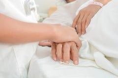 De handen van de het ziekenhuispati?nt aan zorg stock fotografie