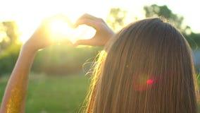 De handen van het zonsonderganghart De vrouw vormt hart met overhandigt zon op zonsopgang of zonsondergang in de aardzomer Meisje stock videobeelden