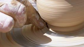 De handen van de hoofdpottenbakker en de vaas van klei op de pottenbakker ` s rijden stock video