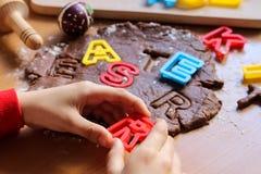 De handen van de jonge jongen snijden koekjes van ruw deeg op een houten lijst met kleurrijke brieven Kokende traditionele Pasen- stock afbeeldingen