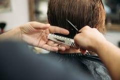 De handen van jonge kapper die tot kapsel maken aan de aantrekkelijke gebaarde mens in herenkapper stock fotografie