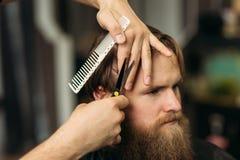 De handen van jonge kapper die tot kapsel maken aan de aantrekkelijke gebaarde mens in herenkapper stock afbeeldingen