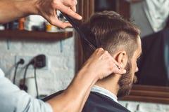 De handen van jonge kapper die tot kapsel maken aan de aantrekkelijke mens in herenkapper Stock Afbeeldingen