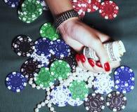 De handen van jonge Kaukasische vrouw met rode manicure bij casino dienen dicht omhoog in Stock Afbeelding