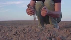 De handen van de jonge landbouwer houden vruchtbare grond op het gebied met graanzaailingen Biologische productenconcept Langzame stock videobeelden