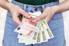 De handen van jonge vrouwen houden euro bankbiljetten