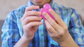 De handen van de jongen kneden, drukken en rekken een roze slijm uit Jongensspelen met slijm stock videobeelden