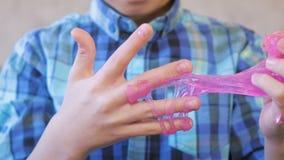 De handen van de jongen met een roze slijm Jongensspelen met slijm stock videobeelden