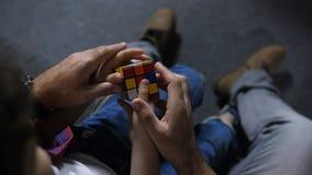De handen van jongen met hulp van papa verzamelen raadselkubus stock video