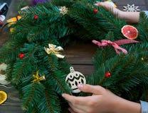 De handen van de jongen snijden rood lint op de houten achtergrond decoratie van de nieuwe jaarkroon stock afbeeldingen