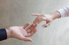 De handen van jonggehuwden met huwelijk stock fotografie