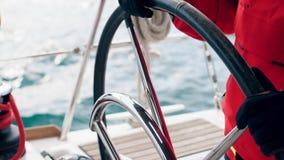 De handen van de kapitein leiden het stuurwiel van het jacht stock footage