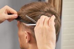 De handen van kapper snijden haar stock afbeelding