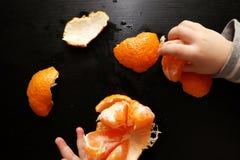 De handen van kinderen borstelen mandarin op een zwarte achtergrond Het kind bereikt voor een plak van mandarin royalty-vrije stock fotografie