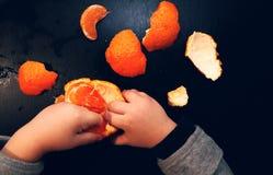 De handen van kinderen borstelen mandarin op een zwarte achtergrond Het kind bereikt voor een plak van mandarin royalty-vrije stock foto