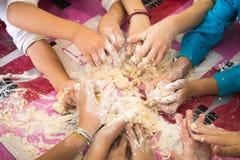 De handen van kinderen, die het deeg verhinderen Stock Afbeelding