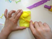De handen van kinderen maken vissen van klei Stock Afbeeldingen