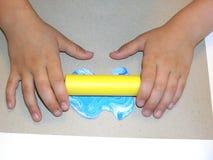 De handen van kinderen met een deegrol Stock Fotografie