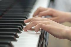 de handen van kinderen spelen de piano De hand van het kind op pianosleutels royalty-vrije stock afbeelding