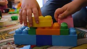 De handen van kinderen verzamelen helder plastic ontwerperclose-up op de vloer van de ruimte Het logische denken Ontwikkeling van stock footage