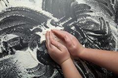 De handen van kinderen werken met bloem aan een zwarte achtergrond, de hoogste mening royalty-vrije stock fotografie