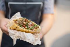 In de handen van de kok, falafel en verse groenten in pitabroodje Stock Afbeelding