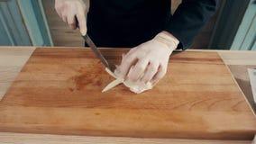 De handen van de kok snijdt van gekookte pijlinktvis Één van de stadia van het koken calamaries de hoogste mening van het zeevruc stock footage
