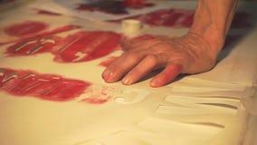 De handen van de kunstenaar legden rode verf op stock videobeelden