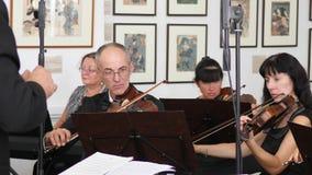 De handen van leiderclose-up, orkest van violisten speelt klassieke muziek en kijken in document blad met muzieknoten stock video