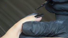 De handen van de manicure behandelen gel-poetsmiddel op de spijkers van de cliënt stock videobeelden
