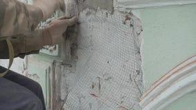 De handen van de mannelijke arbeider maken professioneel metaaldraadnet op groene muur vast stock video