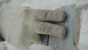 De handen van de mannelijke arbeider pleisteren nauwkeurig grijze muur met groot spacklemes stock footage