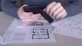 De handen van mannelijke architect, die messege op zijn smartphone typt, sluiten omhoog stock footage