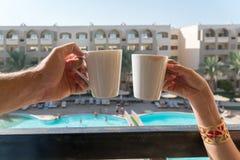 De handen van mannen en vrouwen houden koffiemokken op het balkon op de achtergrond van het hotel, waar de gebouwen en de pool vi royalty-vrije stock foto's