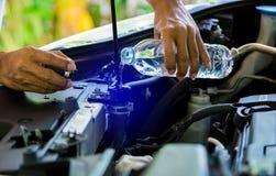 De handen van Mechanisch Check-water in Autoradiator en voegen water aan autoradiator toe royalty-vrije stock foto