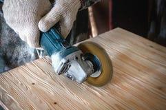 De handen van de meester een boor en een borstel maken hout schoon en geven het textuur Het proces om hout Te borstelen De ruimte royalty-vrije stock fotografie