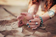 De handen van meisje en weinig groene installatie op barst drogen grond royalty-vrije stock foto's