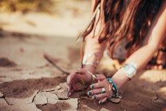 De handen van meisje en weinig groene installatie op barst drogen grond stock afbeeldingen
