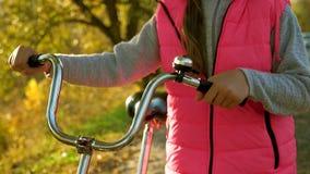 De handen van meisje houden gebogen fietsstuur Close-up meisjesgangen in de herfst in park met een fiets stock videobeelden