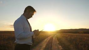 De handen van de mens drijven hun vingers over tablet de mens controleert e-mail Zakenman die aan tablet bij zonsondergang in par royalty-vrije stock foto